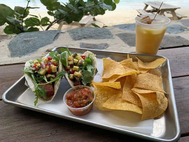 Tacos and chips with a painkiller on the beach